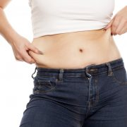 woman pinches her fat on her belly
