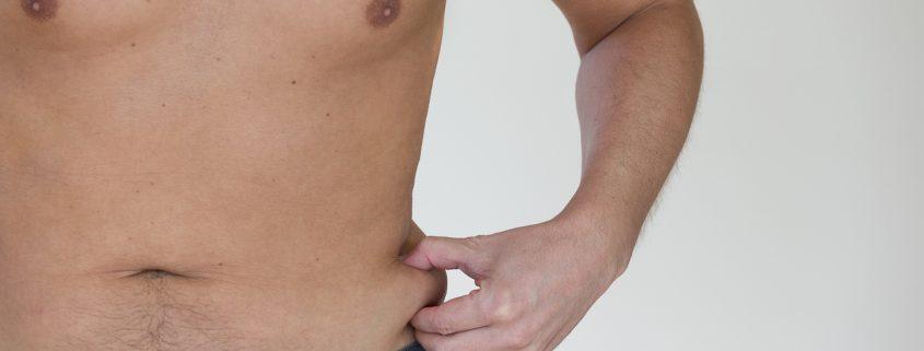 Close up of a man pinching his love handles.